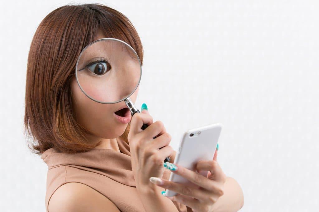 虫眼鏡でスマホを見る女性